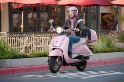 Motociclista da senhora no 'trotinette' cor-de-rosa Foto de Stock