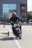 motociclista del L-driver che fa esercizio con i coni sulla terra dell'asfalto Immagini Stock