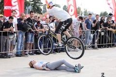 Motociclista di prova che salta sopra la donna Fotografia Stock Libera da Diritti