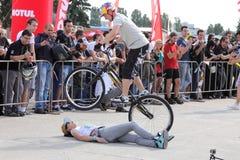 Motociclista di prova che salta sopra la donna Fotografia Stock