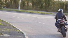 Motociclista do homem novo no por do sol que monta uma motocicleta, em uma curva da estrada rodoviária asfaltada com um fundo rús vídeos de arquivo