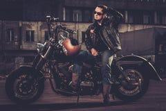 Motociclista ed il suo motociclo di stile del bobber immagini stock