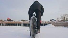 Motociclista estremo professionale dello sportivo che guida una bici grassa nell'aria aperta Giro del ciclista nell'inverno sul g stock footage