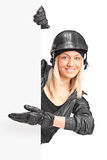 Motociclista femminile che indica su un pannello con la sua mano Immagini Stock