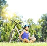Motociclista fêmea novo que senta-se em uma grama ao lado de uma bicicleta e de um drinkin Fotografia de Stock