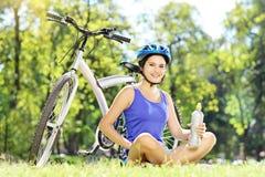 Motociclista fêmea novo que senta-se em uma grama ao lado de uma bicicleta e de um drinkin Foto de Stock Royalty Free