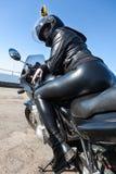 Motociclista grazioso della ragazza in attrezzatura nera ed in casco di cuoio che si siedono sulla bici, retrovisione con bottino immagini stock