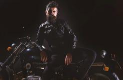 Motociclista macho, brutal no suporte do casaco de cabedal perto da motocicleta na noite, espaço da cópia Conceito da cultura do  imagens de stock royalty free