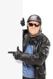 Motociclista maschio maturo che indica su un pannello nero Fotografia Stock Libera da Diritti
