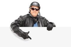 Motociclista maturo che indica su un pannello in bianco Immagine Stock
