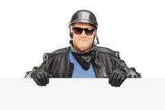 Motociclista maturo che sta dietro un tabellone per le affissioni in bianco fotografia stock