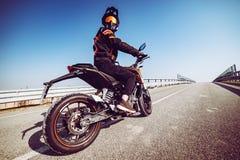 Motociclista na ação que olha traseira na estrada tonificada com um filtro na moda fotos de stock