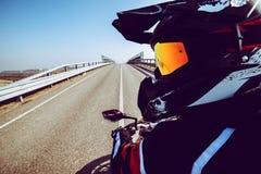 Motociclista na ação que olha traseira na estrada tonificada com um filtro na moda imagem de stock