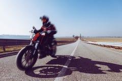 Motociclista na equitação da ação ou do movimento na estrada tonificada com um filtro na moda foto de stock