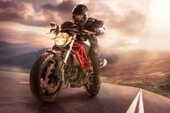 Motociclista na estrada da montanha, montando em torno de uma curva com um borrão de movimento tonificado com um filtro retro app Imagem de Stock