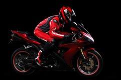 Motociclista nel rosso che guida la sua bici Immagine Stock