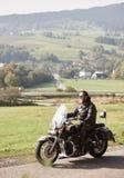 Motociclista no equipamento de couro preto que conduz a motocicleta poderosa moderna ao longo da estrada ensolarada no dia de ver foto de stock