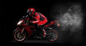Motociclista no vermelho que monta sua bicicleta Imagens de Stock