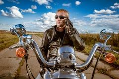 Motociclista que fala em um smartphone imagem de stock