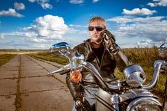 Motociclista que fala em um smartphone fotografia de stock royalty free
