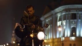Motociclista que senta-se na motocicleta e que põe sobre seu capacete filme