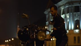 Motociclista que senta-se na motocicleta e que põe sobre seu capacete no movimento lento video estoque