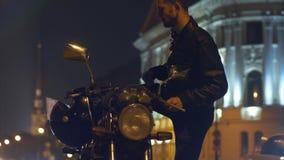 Motociclista que senta-se na motocicleta e que põe sobre seu capacete no movimento lento vídeos de arquivo