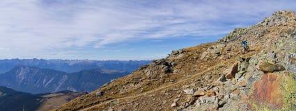 Motociclista que shredding abaixo de uma paisagem áspera da montanha Fotografia de Stock Royalty Free