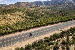 Motociclista solo sulla strada principale del deserto Fotografia Stock Libera da Diritti