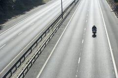 Motociclista su una strada principale vuota Fotografie Stock