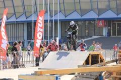 Motociclista sulla pista che juming sul trampolino Fotografia Stock