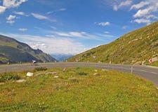 Motociclista sulla strada alpina Immagine Stock