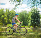 Motociclista superior alegre que monta uma bicicleta em um parque Imagem de Stock Royalty Free