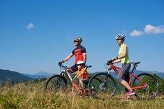 Motociclistas, mamã, paizinho novo e criança do turista da família descansando com bicicletas Fotos de Stock Royalty Free