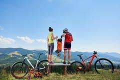 Motociclistas, mamã, paizinho novo e criança modernos dos turistas da família descansando em bicicletas Foto de Stock Royalty Free