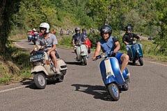 Motociclistas que montam o Vespa do 'trotinette' do vintage Imagens de Stock