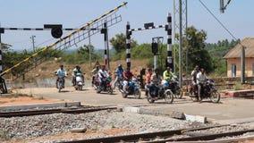Motociclisti che attraversano la ferrovia indiana fotografie stock libere da diritti