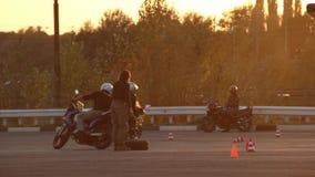 Motociclisti della gimcana di Moto di lezioni di azionamento del motociclo al tramonto archivi video