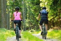 Motociclisti in foresta che cicla sulla pista Fotografie Stock
