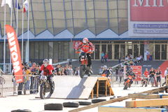Motociclisti sulla pista che juming sul trampolino Fotografia Stock