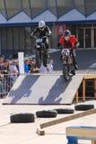 Motociclisti sulla pista che juming sul trampolino Immagine Stock Libera da Diritti