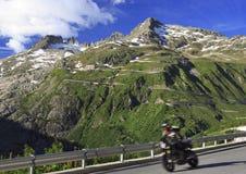 Motociclo ad alta velocità che passa sopra la strada del passaggio di Furka nelle alpi della Svizzera Fotografie Stock