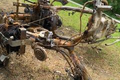 Motociclo bruciato che mette sui precedenti al suolo dell'immondizia del metallo Fotografie Stock Libere da Diritti