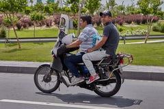 Motociclo con due passeggeri che viaggiano sulla strada principale, Teheran, IRA Immagini Stock