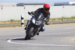 Motociclo di guida del giovane nell'uso della curva della strada asfaltata per il maschio a Fotografie Stock Libere da Diritti