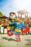 Motociclo felice di guida della bambina sul campo da giuoco da solo in tempo soleggiato Immagini Stock Libere da Diritti