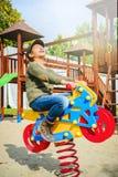 Motociclo felice di guida della bambina sul campo da giuoco da solo in tempo soleggiato Immagine Stock