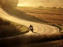 Motociclo sulla strada alla sera di autunno Immagini Stock Libere da Diritti