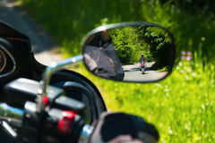 Motociclo sulla strada rurale nello specchio Immagini Stock