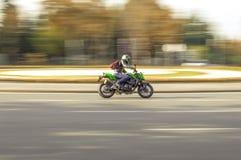 Motociclo verde ad una rotonda fotografie stock